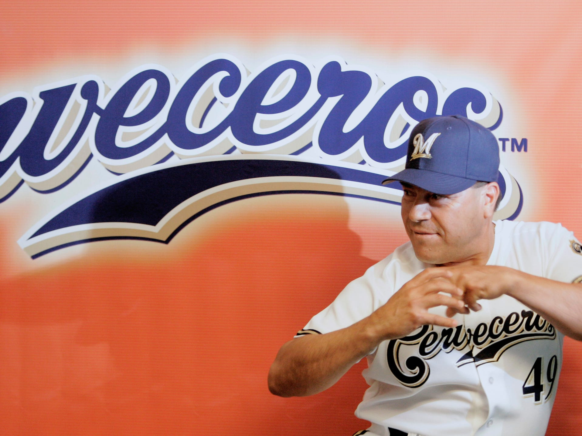 Former Milwaukee Brewers pitcher Teddy Higuera strikes a pitching pose during a press conference to announce the details of 2 events that will pay tribute to legendary African-American and Hispanic players who made contributions to baseball in 2006.