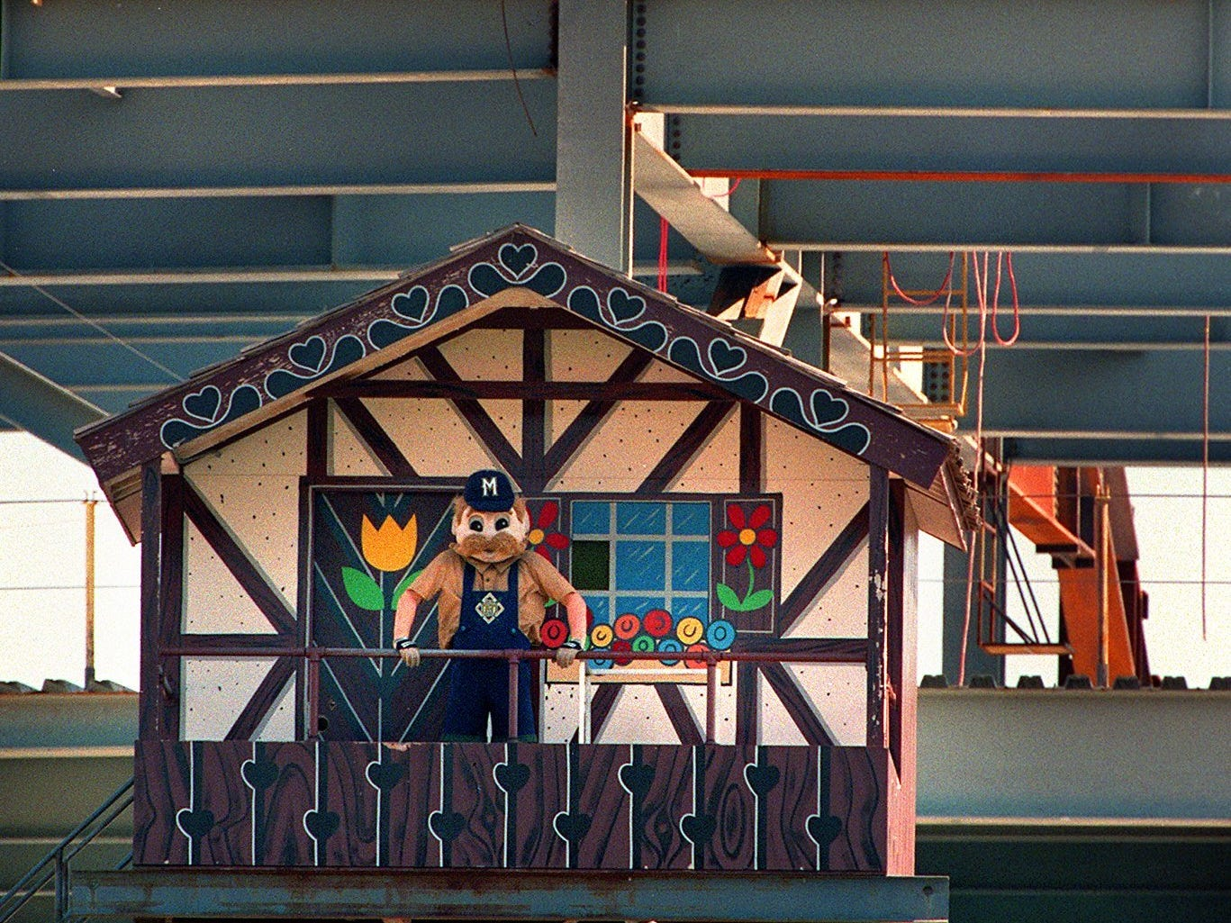 Bernie Brewer and a construction worker watch from their vantage points as the Cincinnati Reds take on the Brewers as seen from County Stadium.