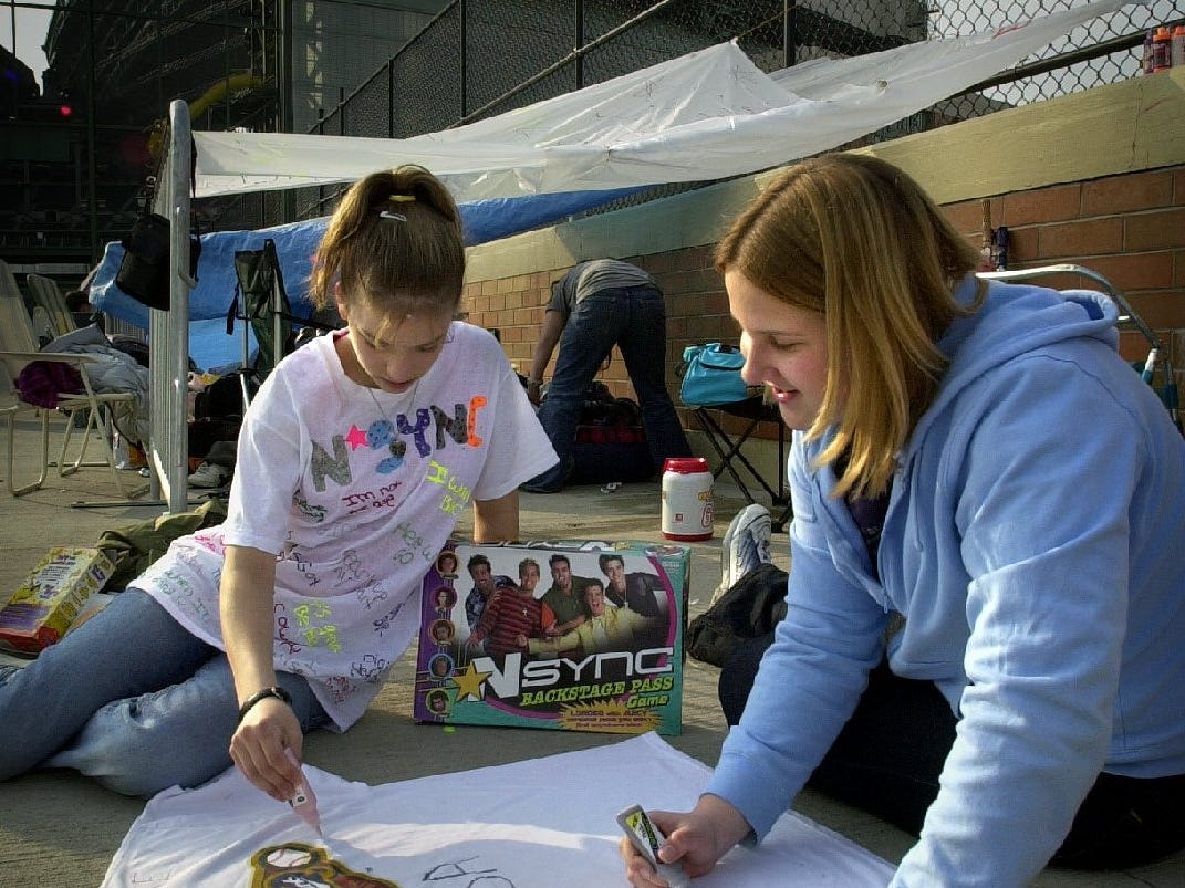 Adina Bratel, 14, (left) and Molly Stikl, 13, both of Greendale, decorate a T-shirt as they wait in line at Miller Park to buy NSYNC concert tickets April 20, 2001.