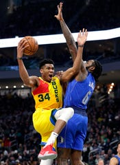 Bucks forward Giannis Antetokounmpo gets around Mavericks center DeAndre Jordan for what turns out to be a twisting underhanded layup that he makes during the second quarter on Monday.