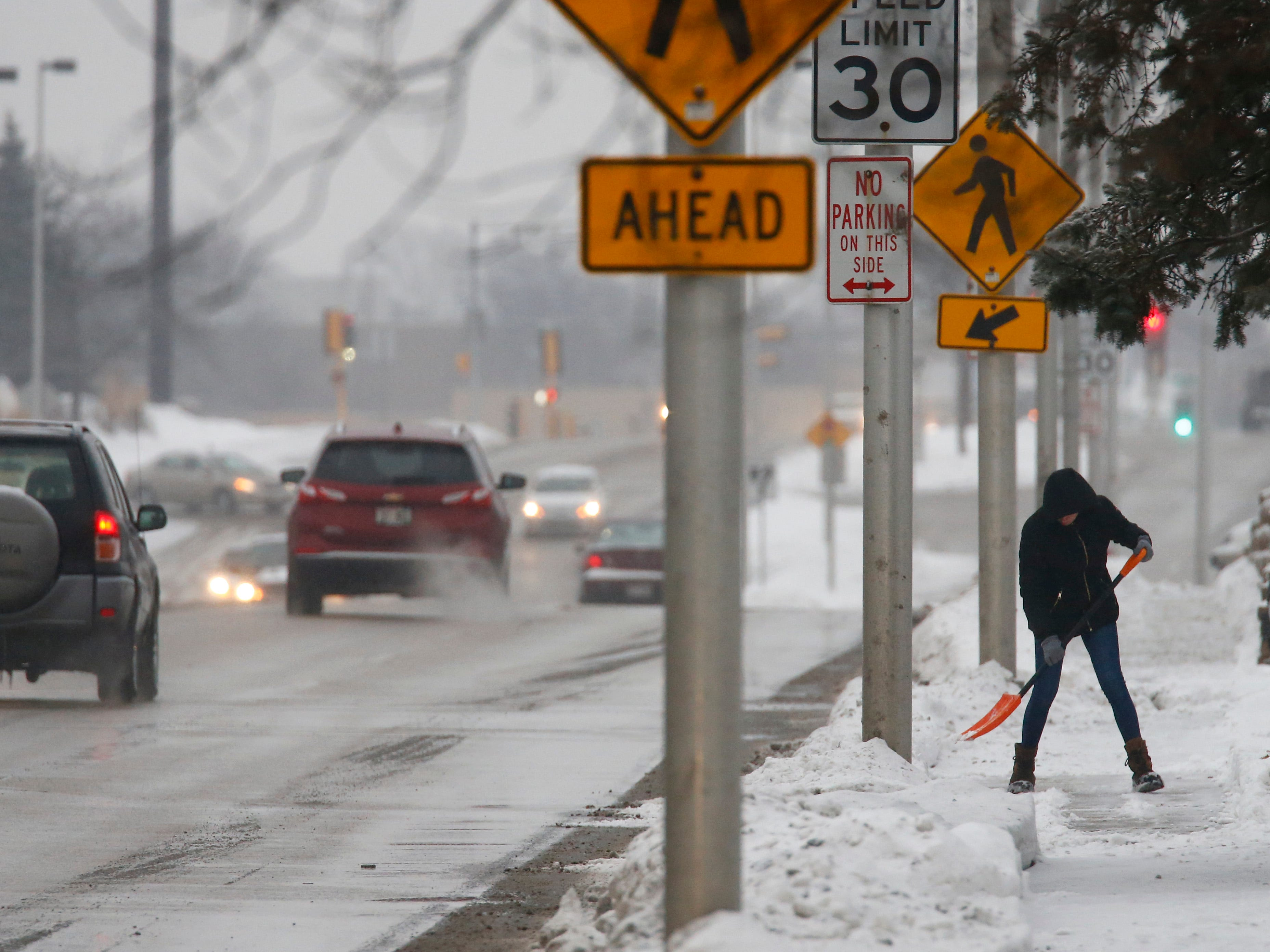 A shoveler clears an Appleton Avenue sidewalk as snow from the Jan. 22 snowstorm begins to fall.