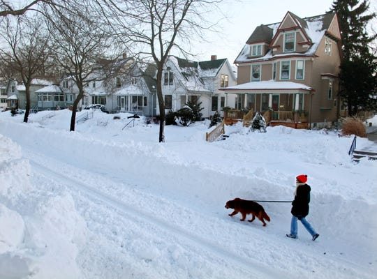 Bayview neighborhood was particularly hard hit by the storm. A woman walks her dog in the 2900 block of South  Superior Street across from South Shore Park, under 4 feet of snow and reduced to one one late Wednesday, February 2, 2011 following a paralyzing storm that hit  southeast Wisconsin.  Rick Wood/RWOOD@jOURNALSENTINEL.COM
