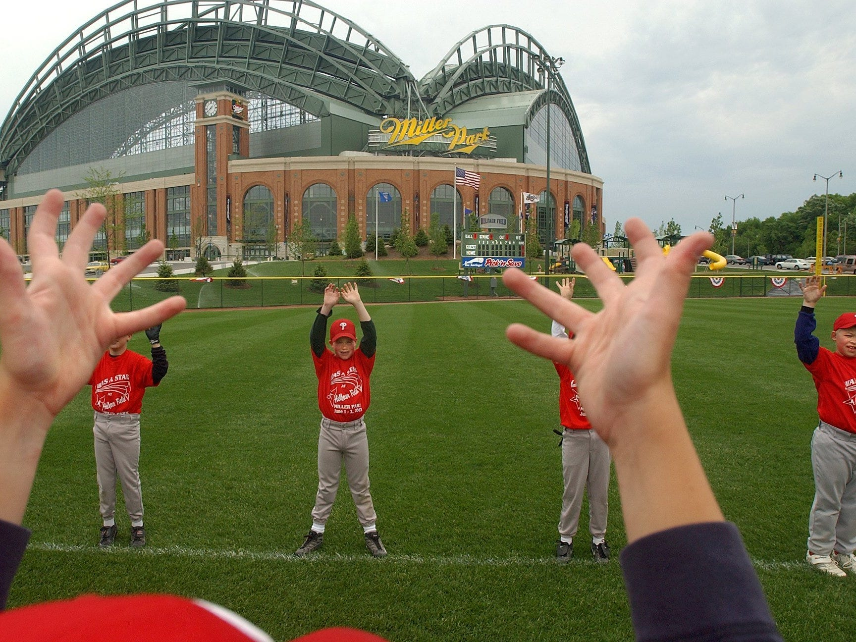 Red team player Chris Coon, 10, of the North Central Little League, leads his teammates through stretching exercises before their game at Helfaer Field, next to Miller Park on Sunday, June 2, 2002. It was the inaugural weekend for play at the new youth ball field.