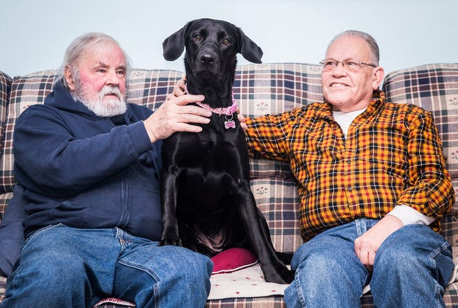 Larry Beswick (left) and James Turner sit with service-dog-in-training Gracie at Turner's home in Muncie.