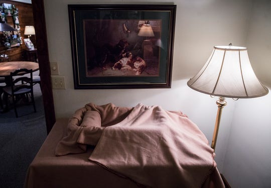 """Rob Loose of Loose Funeral Homes arranges a bed used for pet """"viewings"""" before cremations occur."""