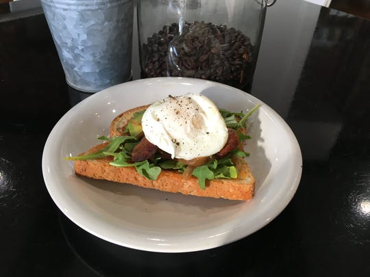 Avocado toast has pepper jelly, bacon, arugula, caramelized onions and a poached egg.