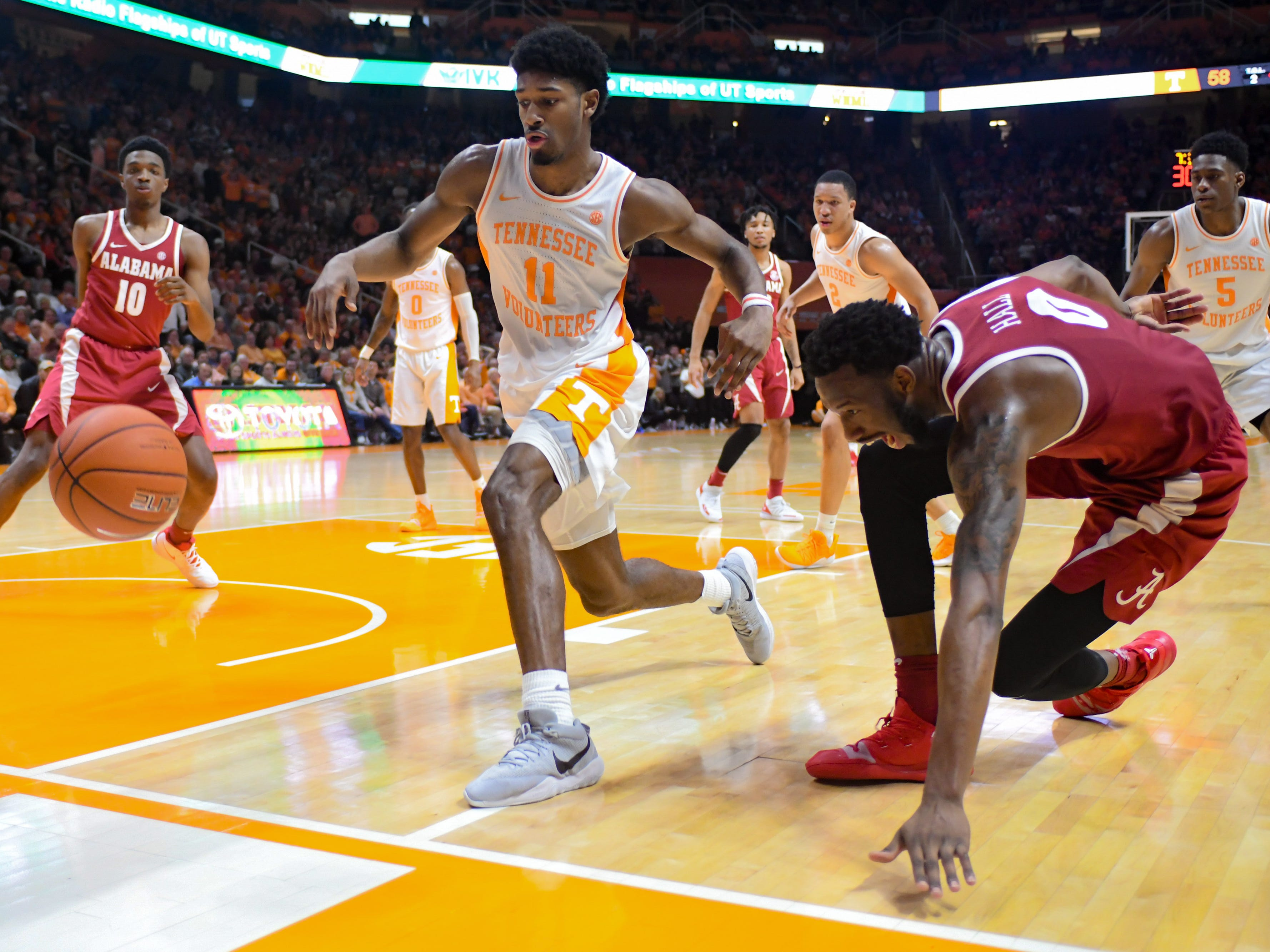 Tennessee Volunteers forward Kyle Alexander (11) and Alabama Crimson Tide forward Donta Hall (0) chase a loose ball during the second half at Thompson-Boling Arena.