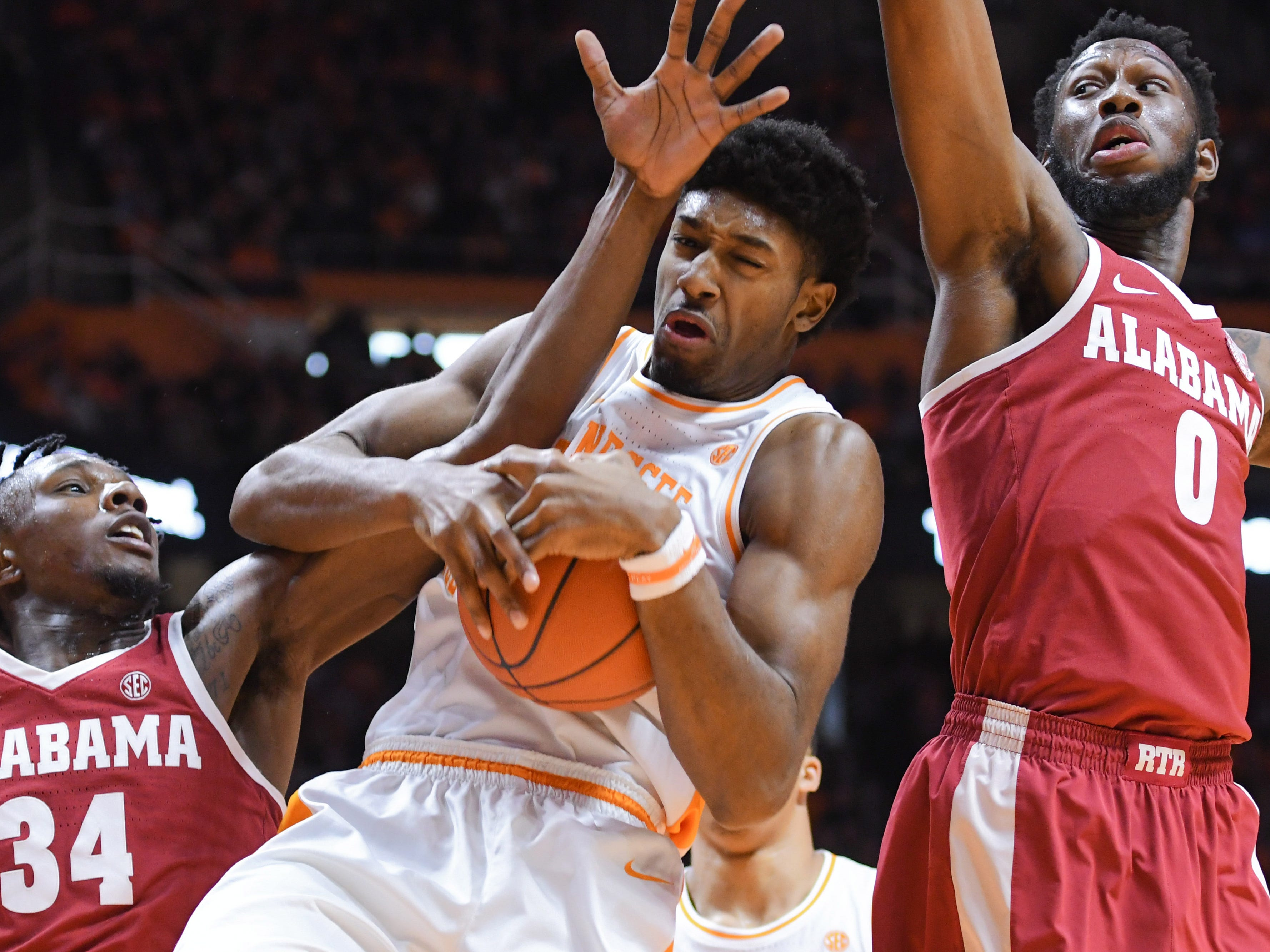 Alabama Crimson Tide guard Tevin Mack (34) and forward Donta Hall (0) battle Tennessee Volunteers forward Kyle Alexander (11) for a rebound during the first half at Thompson-Boling Arena.
