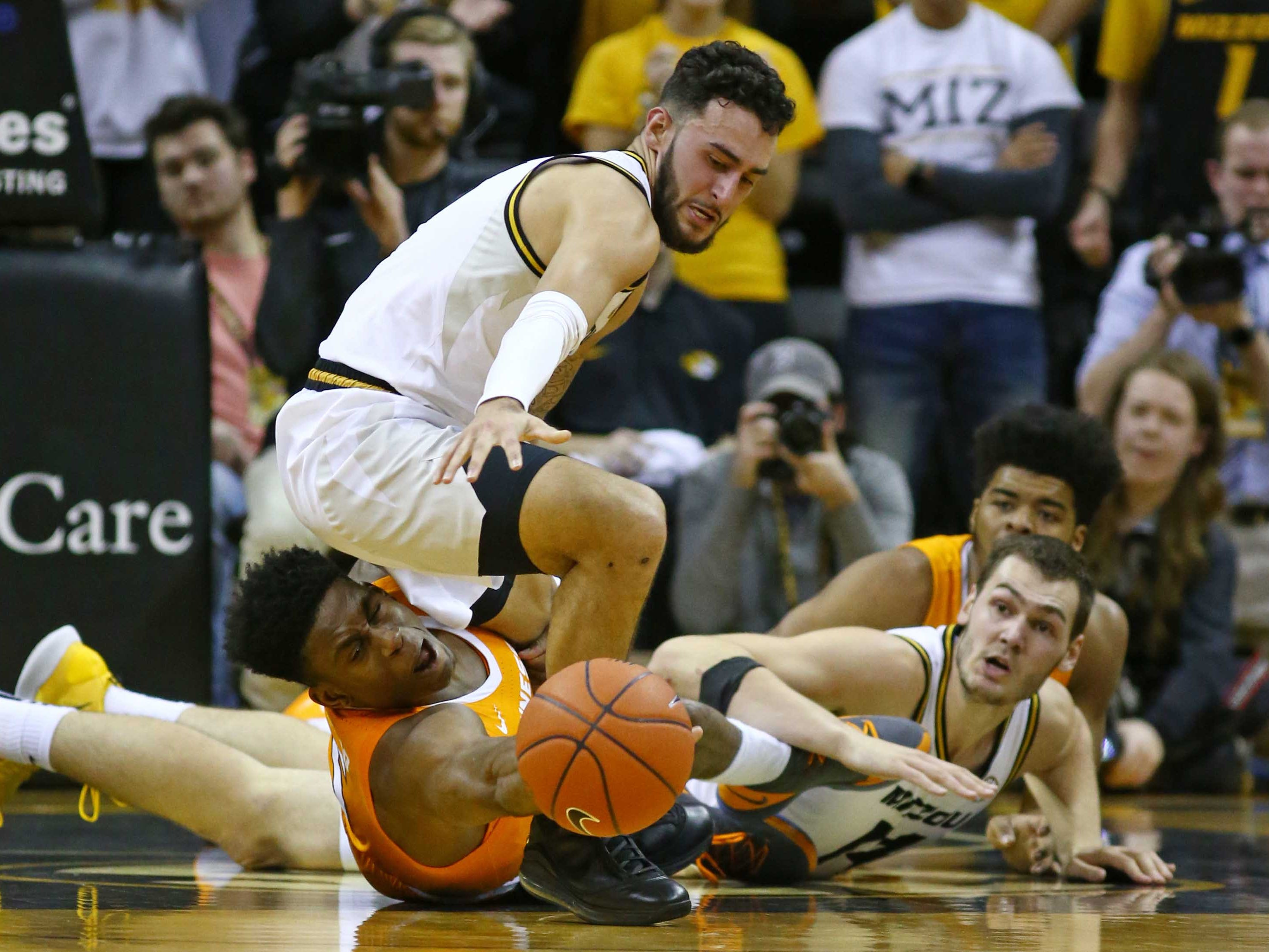 Missouri Tigers guard Jordan Geist (15) and forward Reed Nikko (14) go after a loose ball against Tennessee Volunteers guard Admiral Schofield (5) and forward Derrick Walker (15) in the first half at Mizzou Arena.