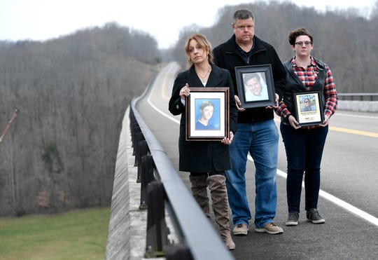 Trish Merelo, Steven Hinesley and Sarah Elmer stand together on the Natchez Trace Bridge holding photographs of family members who died by suicide by jumping off the bridge.