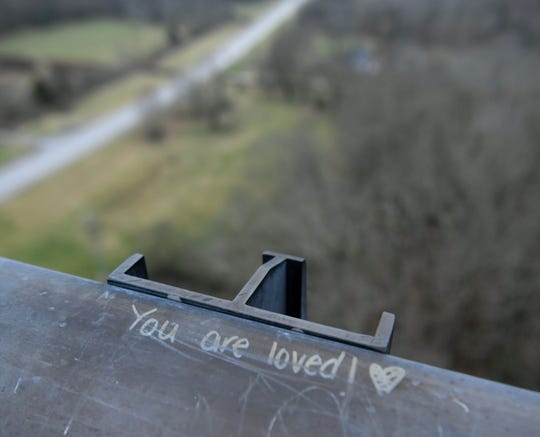 People have written messages on the railing of the Natchez Trace Bridge where 32 deaths have occurred since 2000.