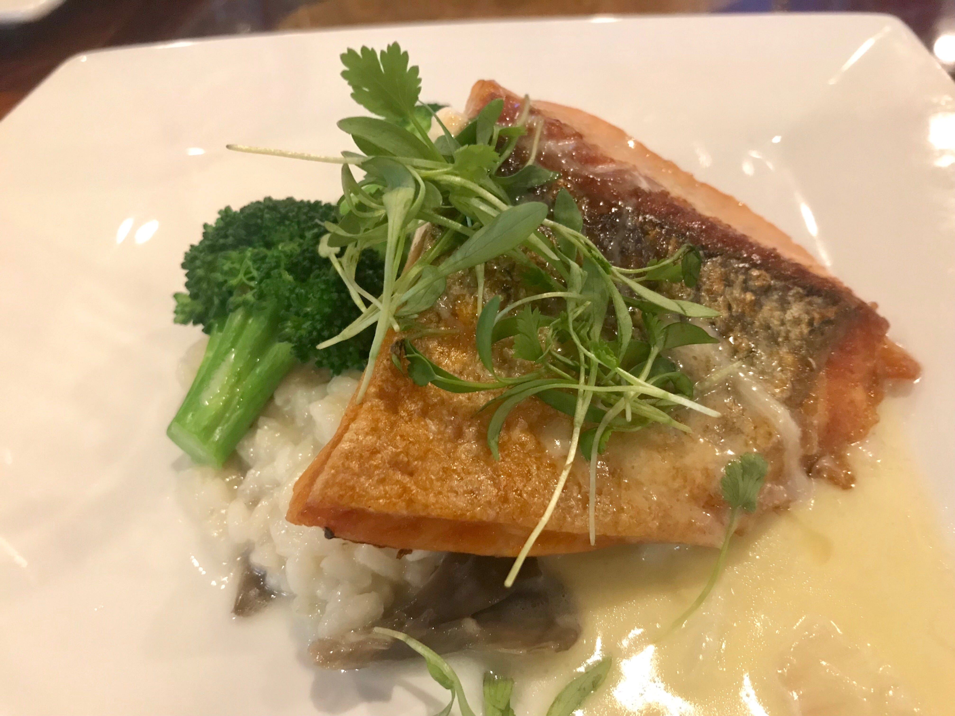 Salmon with a crisp outer layer over mushroom risotto at Drop the Anchor seafood restaurant in North Naples.