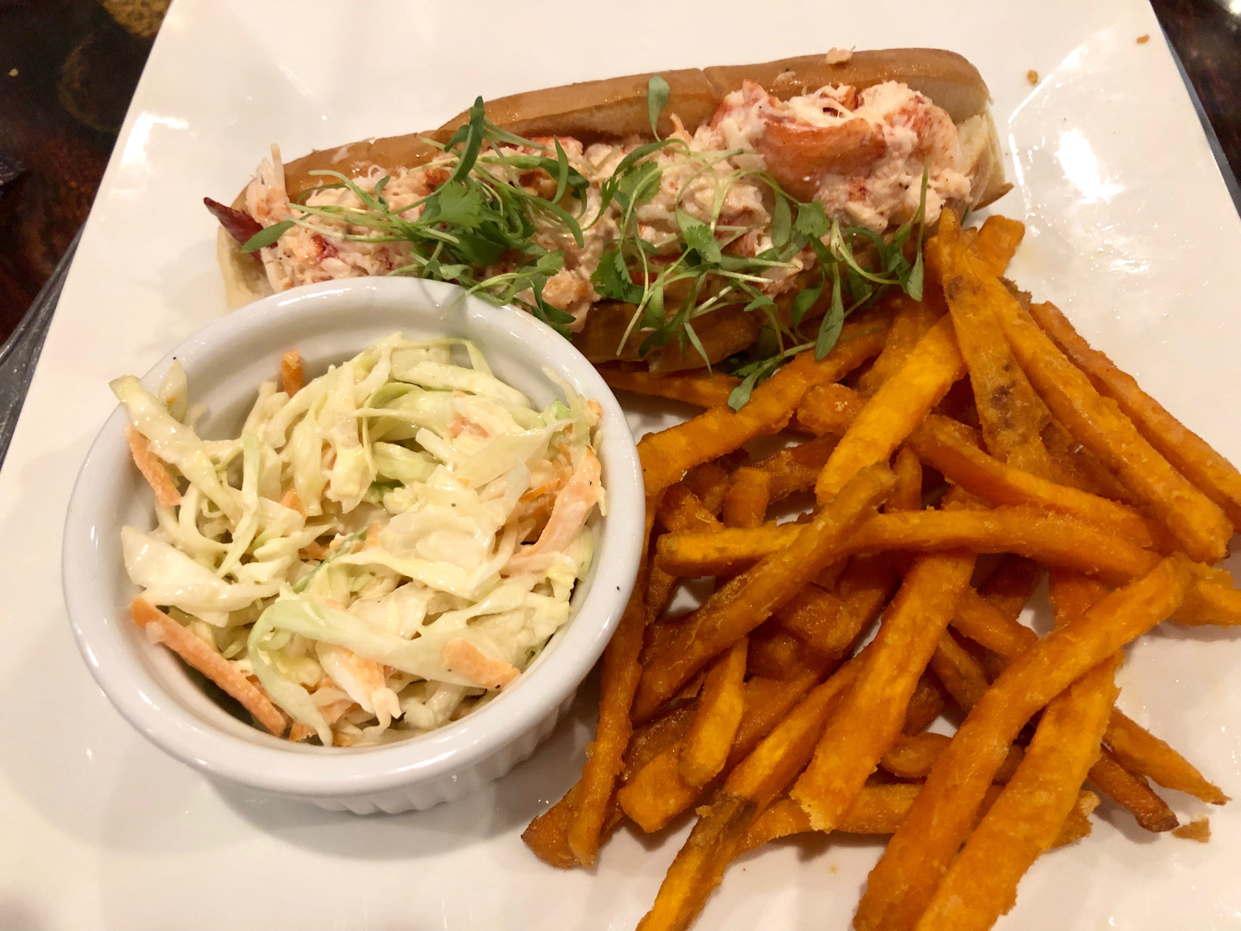 A lobster roll with sweet potato fries and slaw at Drop the Anchor seafood restaurant in North Naples.