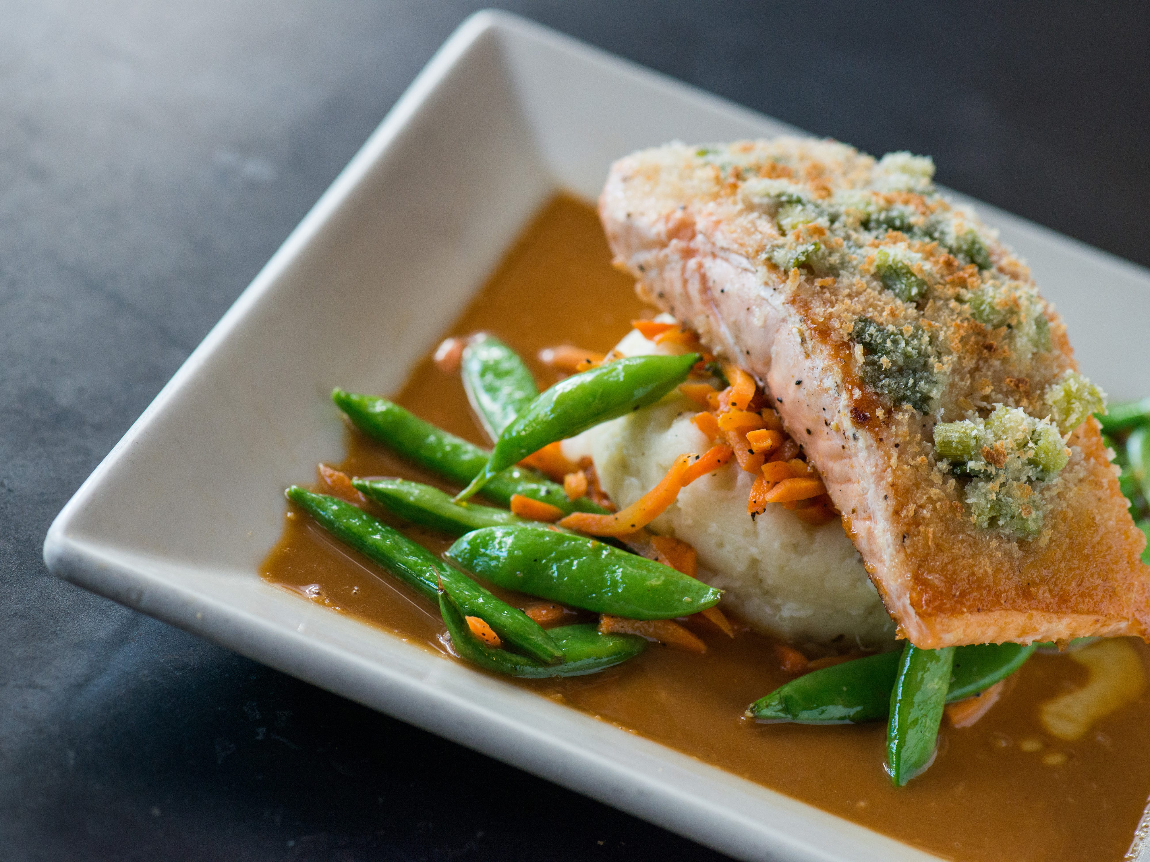 Yard House's Ginger Crusted Salmon includes wasabi mashed potatoes, snap peas, carrots and spicy peanut vinaigrette.