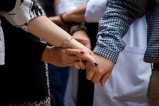 Gina Teegarden, assistant chief nurse, Michelle Cunningham, APC coordinator, and Matt Rudy, histology lab manager, hold hands as a show of solidarity during a rally organized by employees at NCH Baker Hospital Downtown in Naples on Tuesday, January 22, 2019.