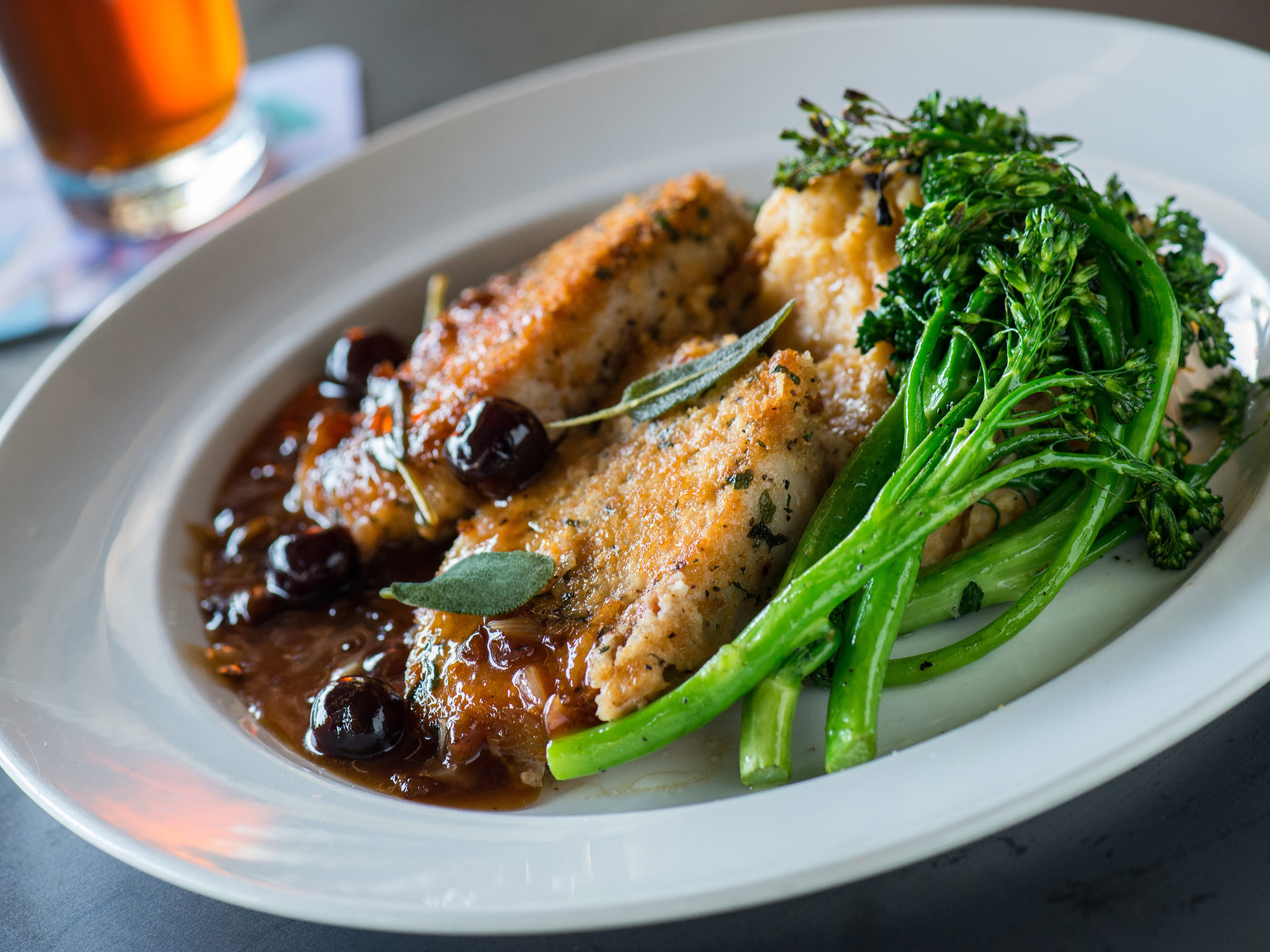 Yard House's Parmesan Crusted Pork Loin features bourbon-sage-cherry-shallot sauce, broccolini and mashed sweet potatoes.
