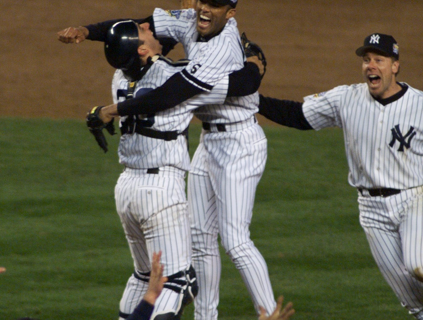 Jorge Posada embracing Mariano Rivera, center, as Scott Brosius, right, and the rest of the Yankees rush the mound after completing a World Series sweep of the Atlanta Braves  in1999.