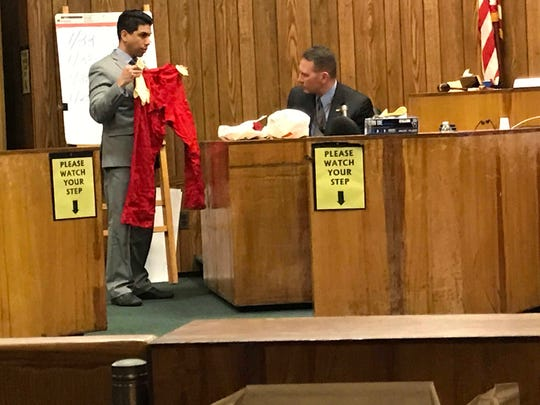 Assistant Prosecutor Jonathan Barrera shows former Clifton detective James Scartozzi the red pants the alleged victim was wearing 19 years ago.
