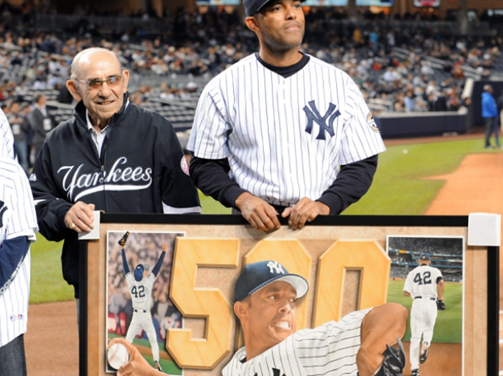 Yogi Berra and Mariano Rivera with a painting of Mariano.   New York Yankees against the Kansas City Royals at Yankee Stadium.