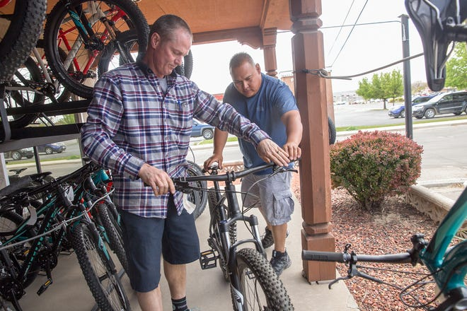 Mike Wulfert, left, helps costumer Matthew Yazzie with a bike selection April 17, 2017, at his store 505 Cycles in Farmington.