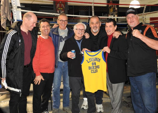 Celebrating a surprise 80th birthday, boxing trainer Paul Soucy (middle) reunites with his former fighters from the Livonia Boxing Club.