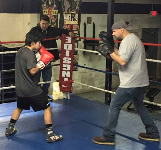 Dynamic Boxing Club trainer Chad Jacquillard (right) works the mitts with 15-year-old Alejandro Mijes.