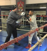 Trainer Tony Colina (left) works out pro fighter Ja'Rico O'Quinn at Dynamic Boxing Club in Westland.