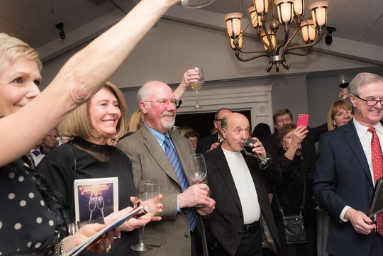Attendees at the farewell to the Courthouse Grille celebration joined in on a toast to Sam Messina.