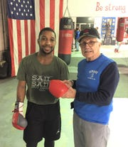 Dynamic Boxing Club trainer Paul Soucy laces up the gloves for 2016 Detroit Golden Gloves champ Robert Rivers during a recent training session.