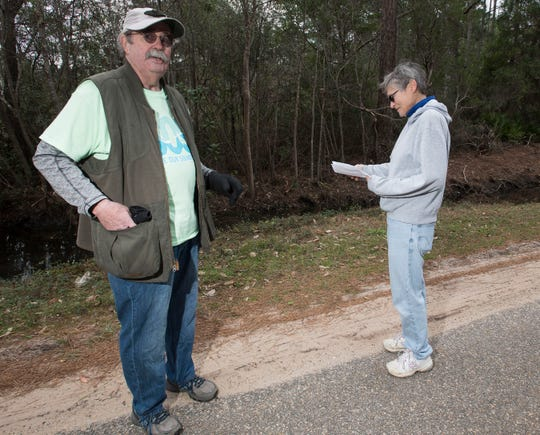 Gulf Breeze resident Michael Brower talks Tuesday about his concerns for a new development planned north of U.S. 98 in Midway as fellow activist Liz Pavelick looks over a site map of the proposed subdivision.