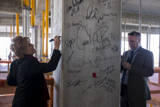 "Pam Giannonatti, Corporate Affairs Manager for Fry's Food Stores, and Phoenix City Manager Ed Zuercher sign a pillar during a ""topping off"" ceremony for the completion of vertical construction of the nine-floor office and retail building at Block 23 on Tuesday, Jan. 22, 2019, in Phoenix."