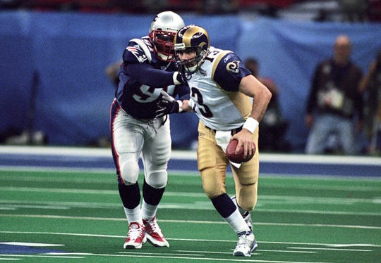Rams quarterback Kurt Warner is chased by Patriots defensive end Bobby Hamilton during Super Bowl XXXVI at the Louisiana Superdome on Feb 3, 2002. The Patriots defeated the Rams 20-17.