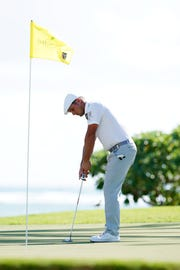 Bryson DeChambeau putts with the flag stick in on the 16th hole during the third round of the 2019 Sony Open in Hawaii golf tournament at Waialae Country Club.