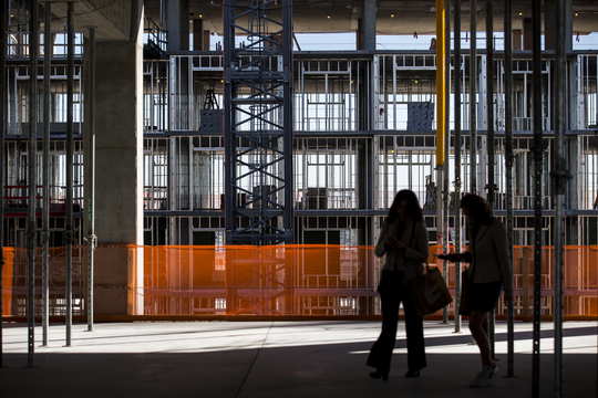 "People walk around after a ""topping off"" ceremony for the completion of vertical construction of the nine-floor office and retail building at Block 23 on Tuesday, Jan. 22, 2019, in Phoenix."