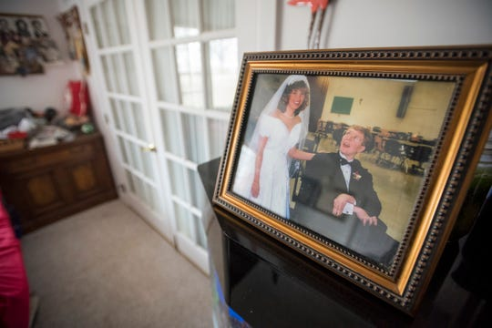 A framed photo of John at his sister Kirsten's wedding in 1997 sits on top of the fishtank in the living room of the Sullivan's Marlette home.