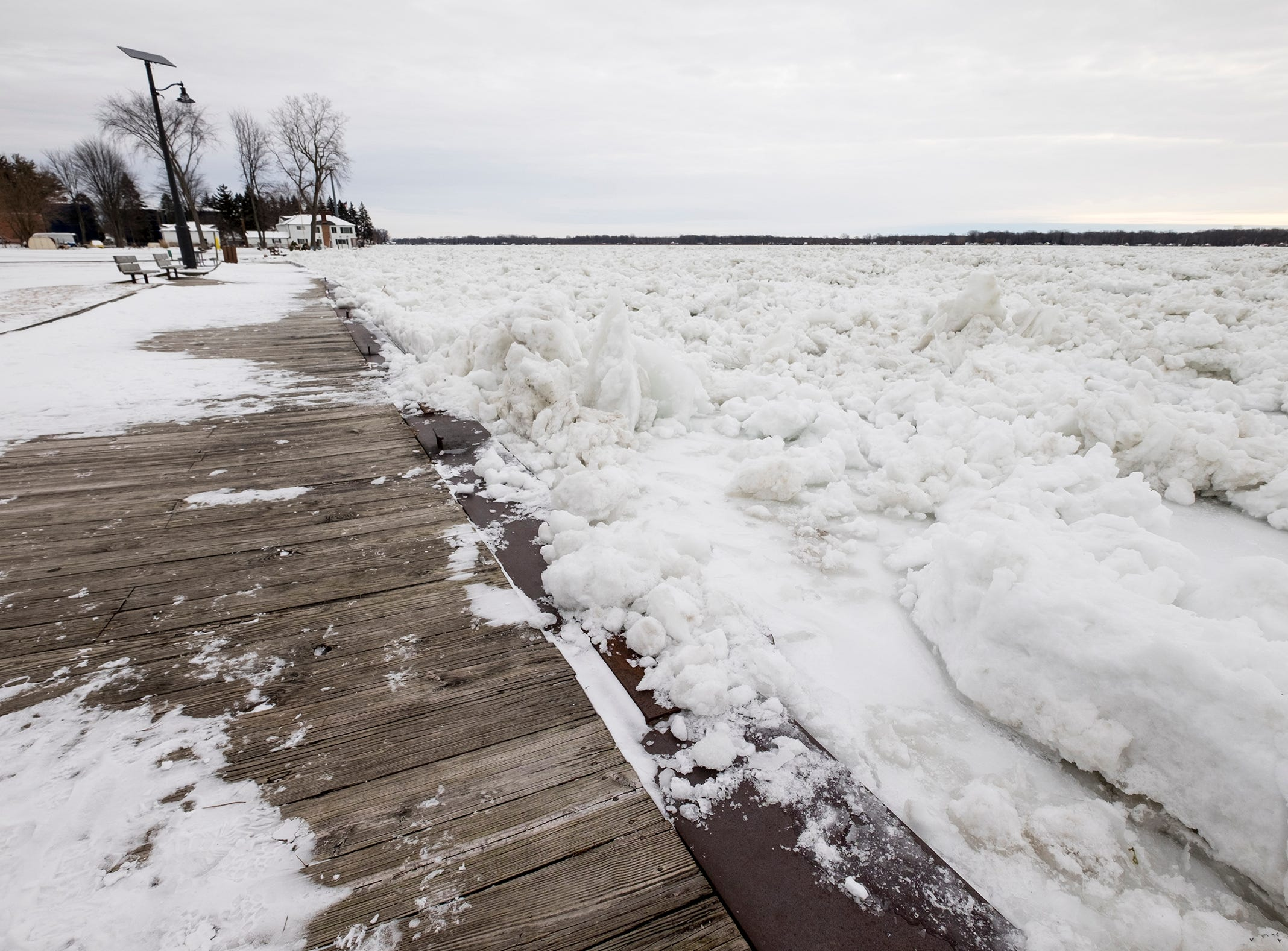 Ice from the St. Clair River spills over onto the boardwalk in Algonac Tuesday, Jan. 22, 2019. An ice jam formed in the St. Clair River near Algonac over the weekend, resulting in climbing water levels and flooding along the river and in canals.
