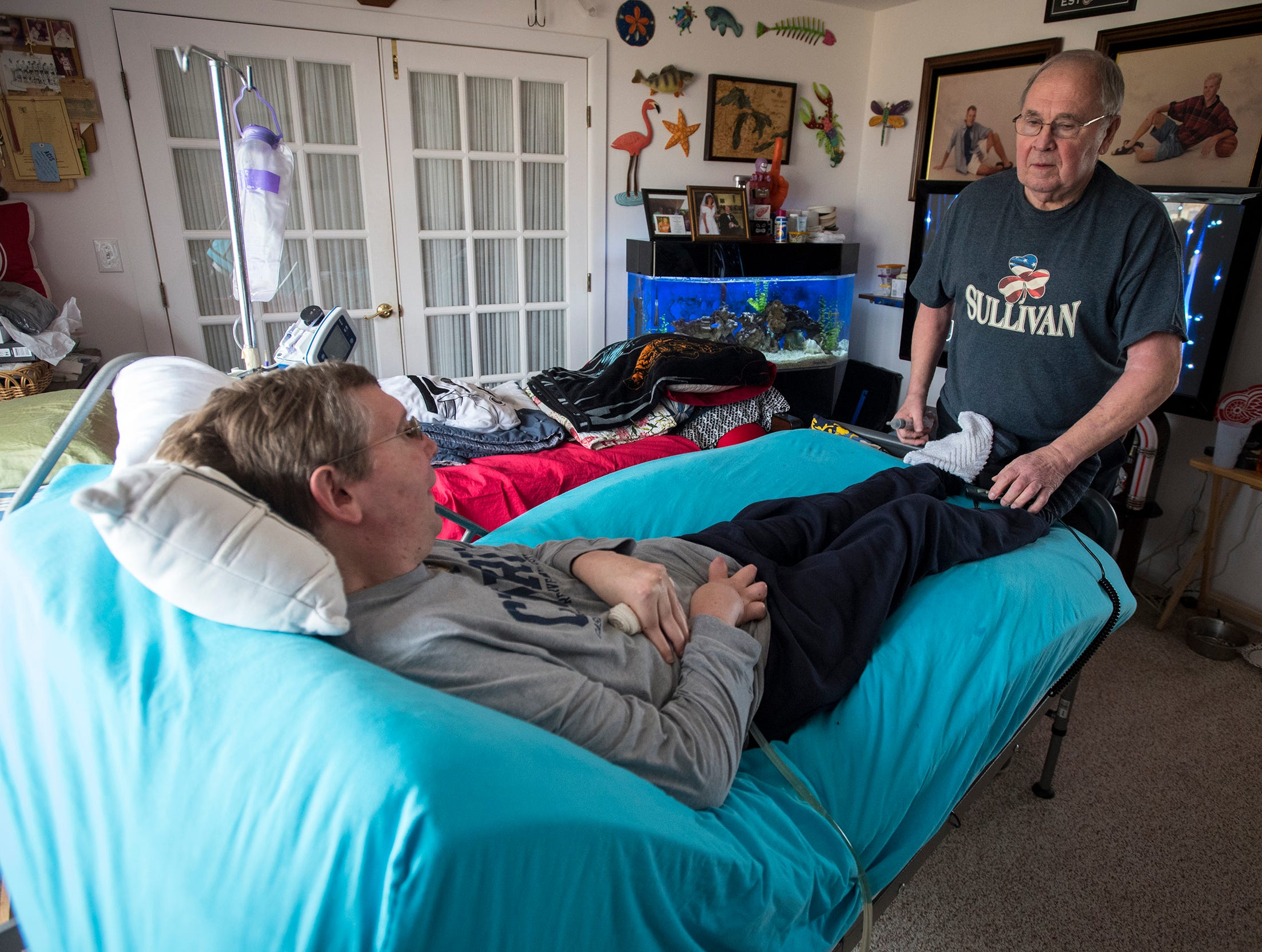 John's father, Richard Sullivan, right, helps make John comfortable in his special bed Thursday, Jan. 17, 2019 at their home in Marlette.