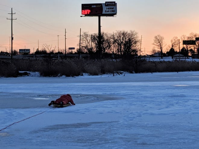 Dive Team Auxiliary member Matt Carpo approaches a hole made by a snow mobile on Jan. 20, 2019.