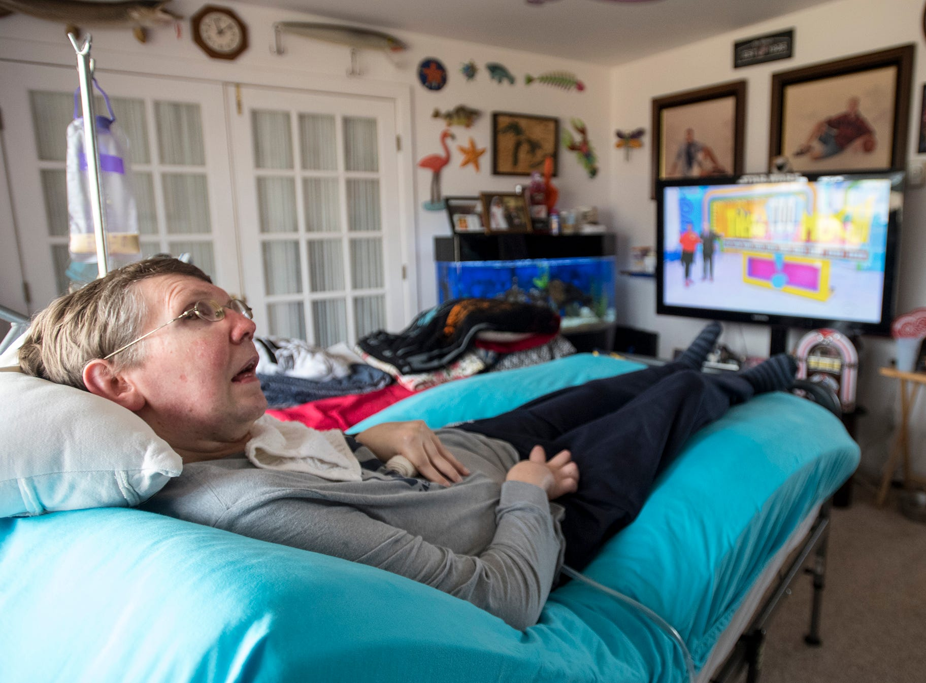 John Sullivan lays on a special bed in the living room of the Sullivan's Marlette home Thursday, Jan. 17, 2019. The big screen television set is left on 24 hours to help keep John calm when he wakes up.