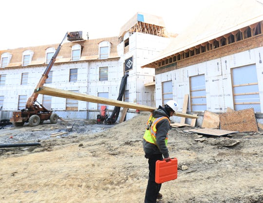 A worker carries a wooden beam at the construction site of Mirbeau Inn and Spa in Rhinebeck on January 16, 2019.