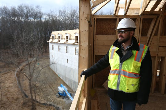 Jonathan T. Dal Pos, partner with Mirbeau Hospitality Services looks out over the woods behind the site of Mirbeau Inn and Spa in Rhinebeck on January 16, 2019.
