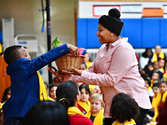 Food Service Manager Azaira Washington claims her non-educator prize as students and staff celebrate during Lincoln Charter's School Choice assembly at the school in York City, Tuesday, Jan. 22, 2019. The donation was designated to benefit students, parents and staff, according to Anne Clark, who is the director of community outreach for the school. Dawn J. Sagert photo