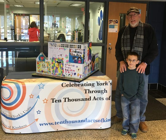 Parker James Hooker with a kindergarten student from Mrs. Ravo's Class at Ore Valley Elementary who won third place in the kindness poster contest that is part of the sculpture.