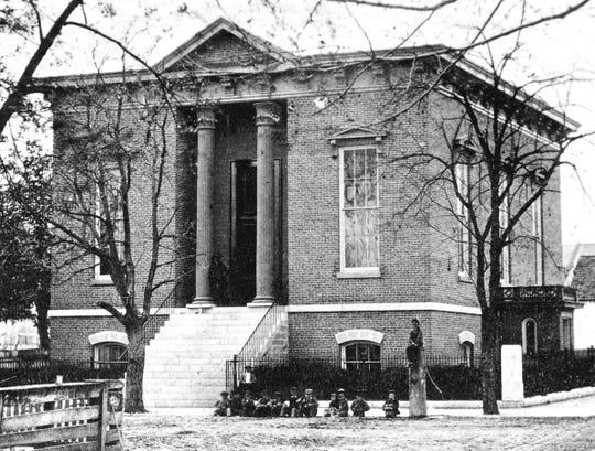 "Original 1864 Morrisson library at the southwest corner of North 6 and A Street before being refurbished according to Carolyn Reeves' wishes. Note the ""street urchins"" outside. There is even a man standing in the doorway leaning against a pillar."