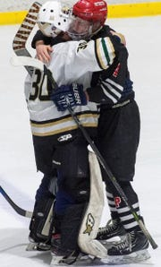 Rush-Henrietta goalie Cameron Kuzniar and Penfield forward Jack Schlifke embrace after the Patriots' 3-1 win over the Royal Comets on Jan. 5. Kuzniar and Schlifke have been teammates on travel teams and competed against each other on the varsity level for the past four seasons.