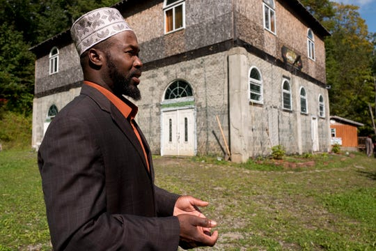 Rashid Clark discusses his Muslim community while standing outside the enclave's mosque in Islamberg, New York. Three Monroe County men are charged with plotting an attack on the enclave 40 miles east of Binghamton. The community is dogged by terror accusations, many spread on right-wing websites.