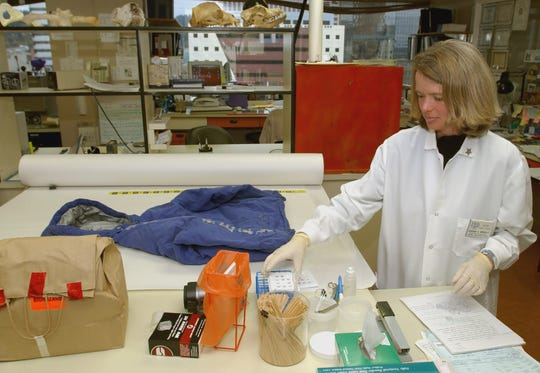 Forensic scientist Deborah Newville examines stains on a coat held in evidence at the state forensic lab in Portland Ore., in 2003.