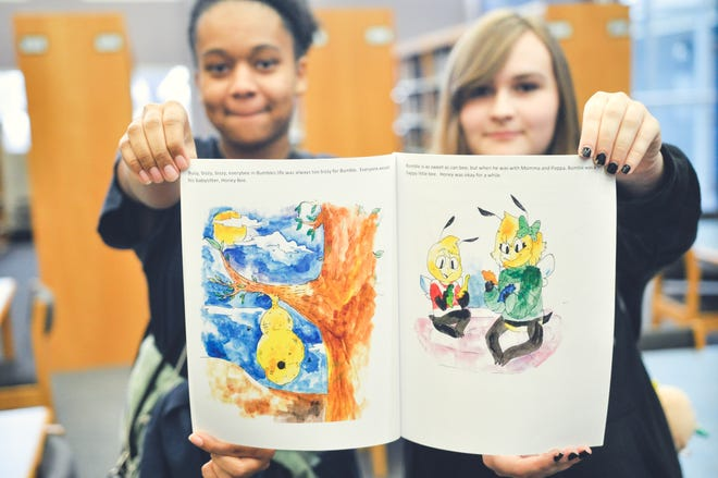 Lake View Writers Club members Ellie Woodruff  and Alayna Gregg show off a copy of the children's book they helped write and illustrate.