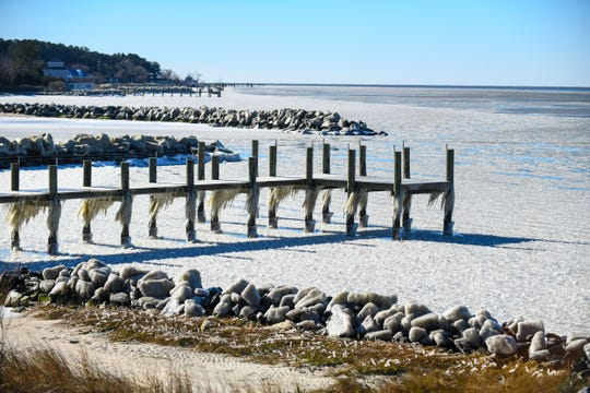 An iced covered pier sits in the frozen Chesapeake Bay on Tuesday, Jan. 22, 2019 in Chance, Md.