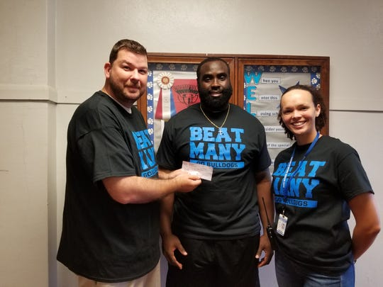 Red River principal J.C. Dickey and assistant principal Tiffany Roque accept a donation from Tennessee Titans defensive end Bennie Logan.